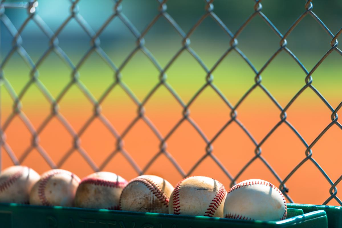 baseballs-lined-up-against-chain-link-fence.