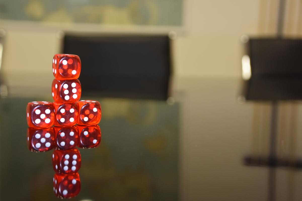 red-dice-stacked-on-a-boardroom-table