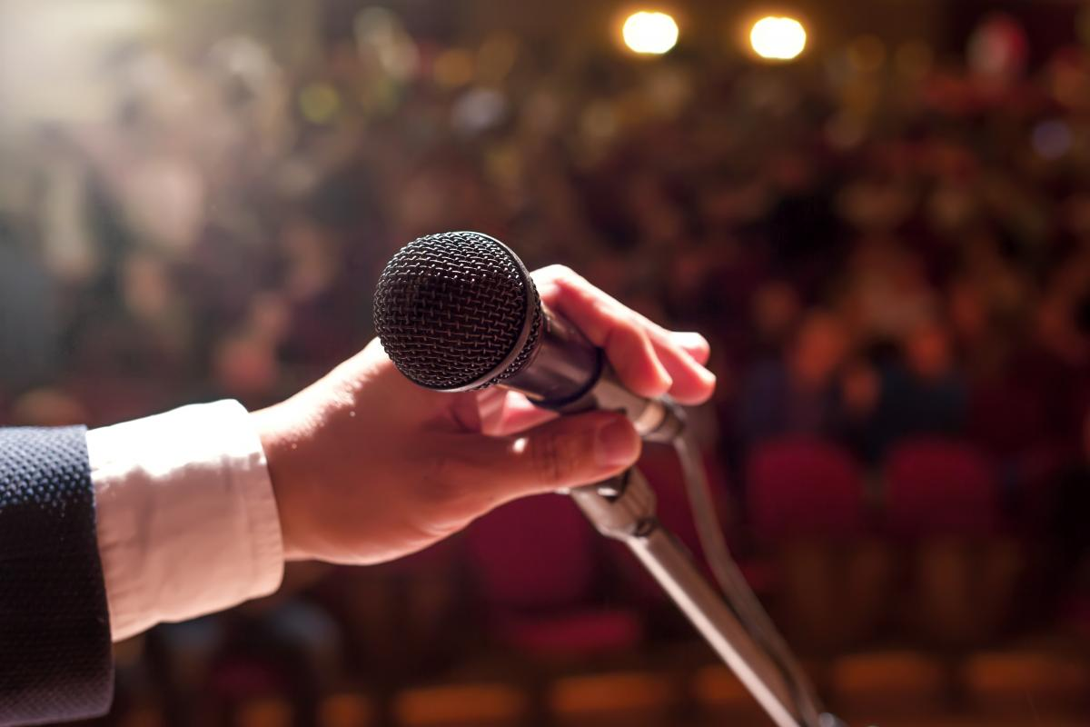 Hand holding microphone in front of crowd